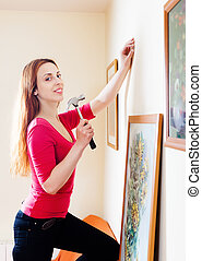 woman hanging the art pictures on wall