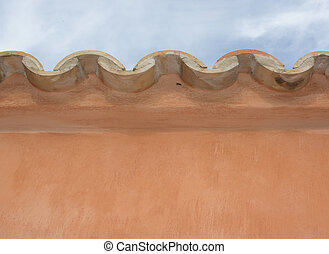 Edge of tiled roof and earthy background wall in Mallorca,...