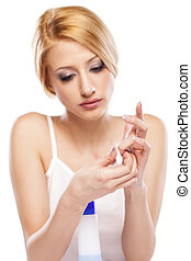 nail care - portrait of a beautiful young woman removing her...