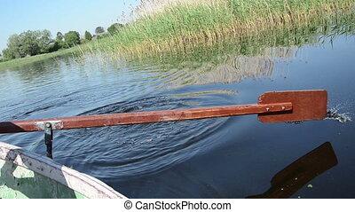 oar on water - oar strikes the water surface rises up spray