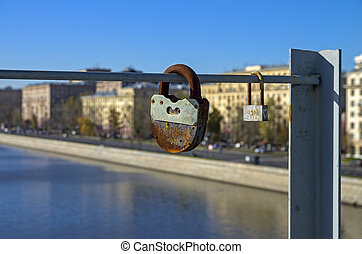 Two love locks - Two love padlocks fixed on a bridge across...