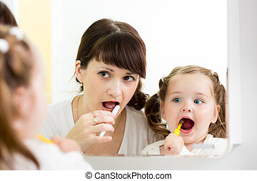 mother teaches child brushing teeth