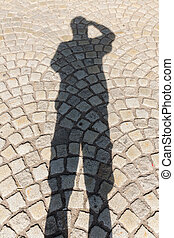 Shadow of a man on pavement