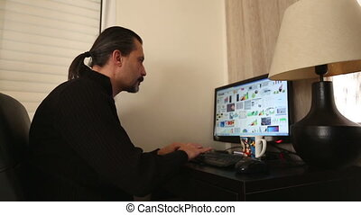 Home Office - worried brunette man working computer at home...
