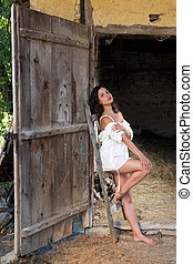Lingerie pose in a grunge barn - Beautiful young woman in...