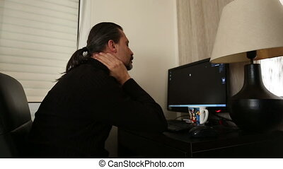 Home Office - brunette man working computer having neck pain...