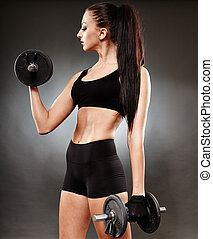Athletic woman working out with dumbbells - Young athletic...