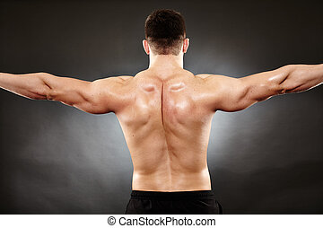 Athletic man doing bodybuilding moves for the back muscles -...