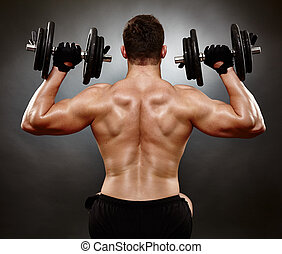 Athletic young man working with heavy dumbbells - Studio...