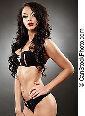 Alluring brunette in black lingerie with hand on hip -...