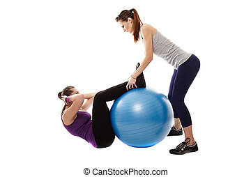Woman doing abdominals helped by the instructor