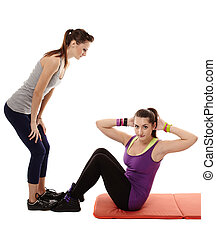 Woman doing abs crunches helped by the personal trainer