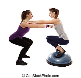 Studio shot of woman doing squats on a bosu ball, helped by...