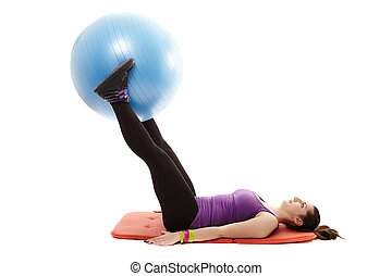 Studio shot of young athletic woman lying on the floor, holding a ball between legs and working out the abdominal muscles, isolated over white background