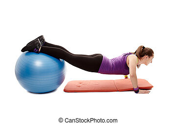 Athletic woman doing pushups with legs on the ball