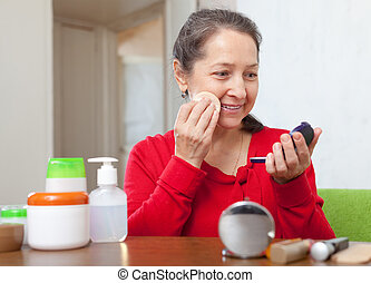 mature woman in red putting facepowder - Smiling mature...