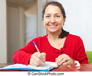 Smiling mature woman fills in documents at home