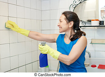mature woman cleans tiled wall - Smiling mature woman cleans...