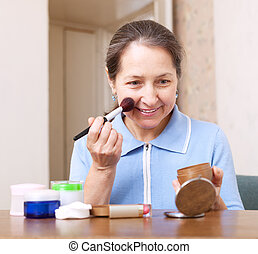woman putting make up on her face - woman putting make up on...