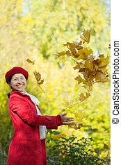 Happy woman throw up maple leaves - Happy mature woman throw...
