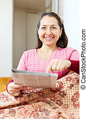 mature woman pointing to newspaper
