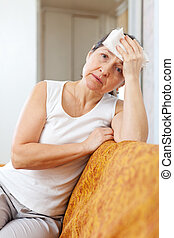Sad mature woman having headache holding towel on her head
