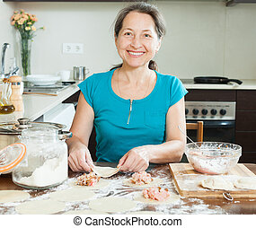 Smiling mature woman making meat dumplings pelmeni at...
