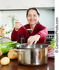 mature woman adding seasoning into lent diet soup - Smiling...