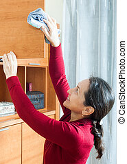 woman cleaning wooden furniture with rag at home