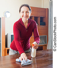 Woman cleaning the table - Happy mature woman cleaning table...