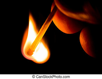 Fire from match in darkness Hand holding match