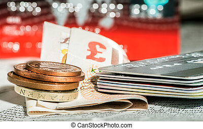 Coins, credit cards and british pounds on newspaper. Macro...