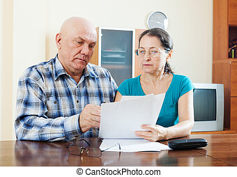 mature man with wife reading  documents