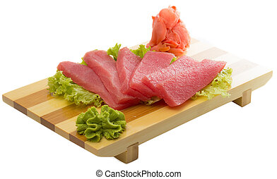 fresh raw tuna fish pieces on wooden plate isolated