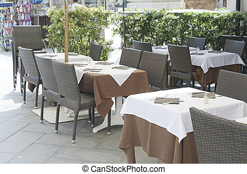 Empty tables of sidewalk cafe in Italia