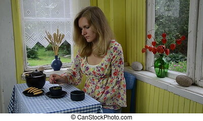 woman drink chamomile tea - Woman mix cup with chamomile...