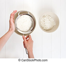 Sifting Flour - A woman sifts white flour through a metal...