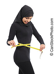 Arab woman measuring waist with a measure tape isolate don a...