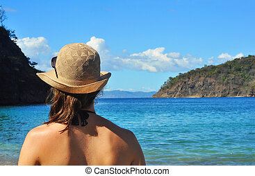 Young womans back looking at the sea - Young womans back,...