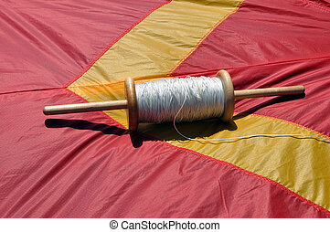 spindle  - A spindle with white thread to fly kites