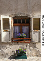 rustic window with old wood shutters and flower pots in stone rural house, Switzerland.