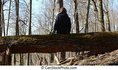 girl sit fallen tree