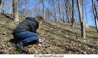 woman pick violet flowers - a woman with a black jacket in...