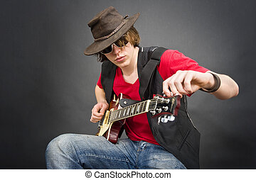 Guitar Tuning - A musician wearing an old leather hat tuning...