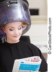 Woman client curlers in hair reads magazine hairdressing...