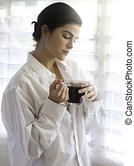 woman by bright window with coffee - woman having morning...
