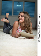 Happy Woman Using iPad While Lying On Carpet - Young Woman...