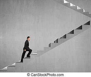 Businessman climbing on concrete stairs with concrete wall...