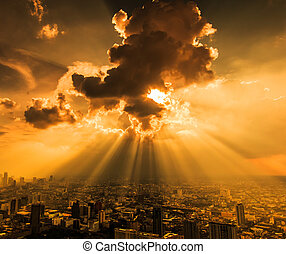 Rays of light shining through dark clouds city Bangkok,...