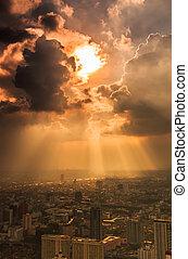 Rays of light shining through dark clouds city Bangkok,...